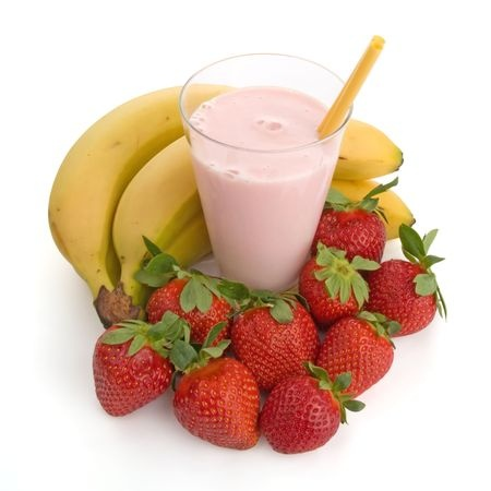 pink smoothie in a glass with straw surrounded by fresh strawberries and bananas