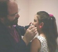 Photo of Dr Ron Cherubino treating a child with red laser therapy