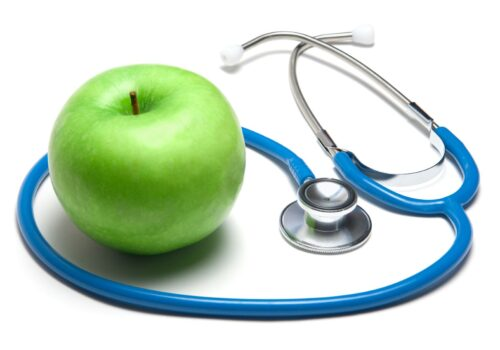 Stethoscope with green apple on white