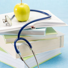 Photo of books stacked with a yellow apple on top and a stethoscope around the Apple