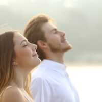 Relaxed couple facing skyward with closed eyes and smiles