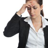 Female with headache holding head