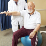 Chiropractor in Framingham wearing white lab coat performing shoulder therapy with an older gentleman on an exercise ball