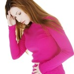 Woman in bright pink sweater holding her stomach as she experiences digestive disorders