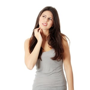 Picture of woman with long brown hair scratching because of a skin conditions