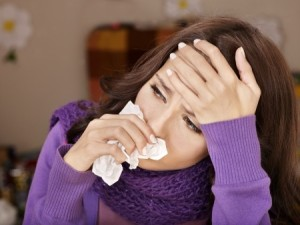 Woman suffering from allergies wipping nose with tissue and holding her head