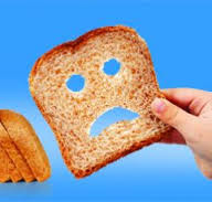 photo of slice pf overprocessed wheat bread with sad face torn out of it