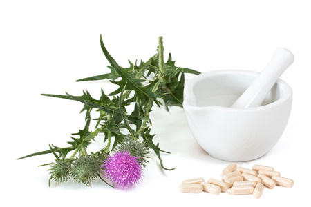 milk thistle with capsules next to mortar and pestle