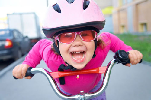 Happy active girl on bicycle wearing helmet